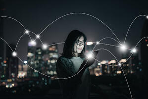 Young girl holding a phone with light streams signifying data migration